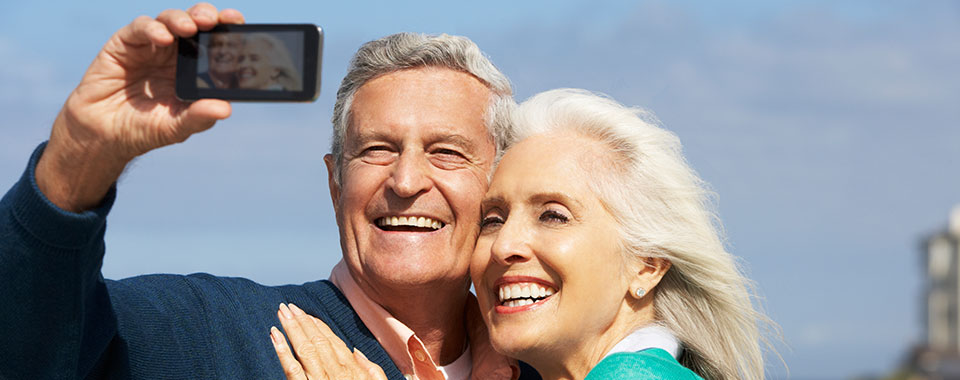 Smiling elderly couple smiling taking a selfie with a smartphone
