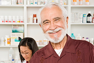 Smiling man at pharmacy with pharmacist standing behind him.